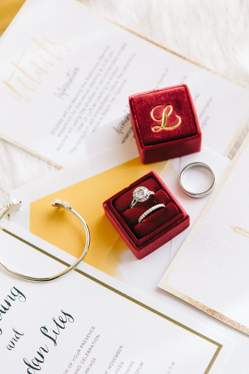 Cranberry ring box with wedding bands and gold details