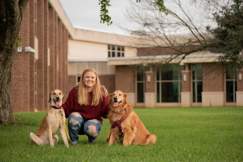 Senior girl crouching with her dogs in front of school