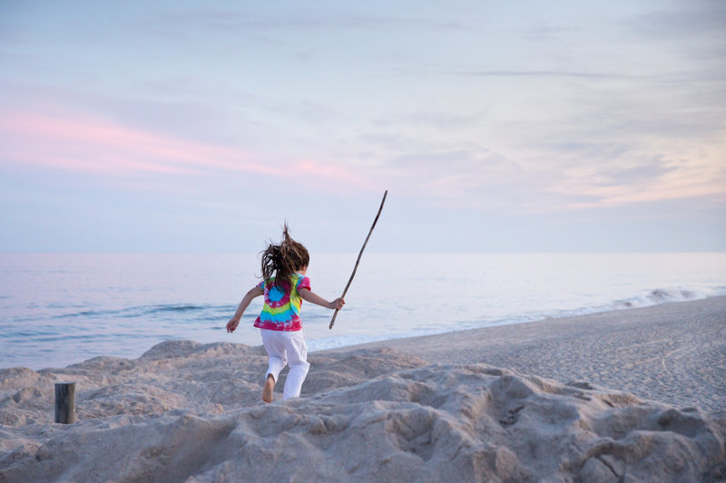 Young boy with long hair holds a stick and jumps off of the dunes at East Hampton Main Beach in East Hampton, NY.