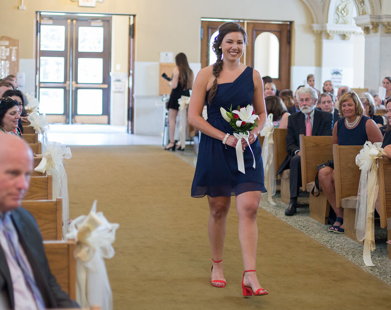 Maid of honor walks down the aisle at a St. Patrick's Church wedding