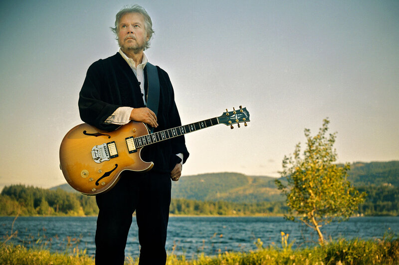 Randy Bachman portrait standing in front of lake arm resting on guitar slung over shoulder small tree beside him