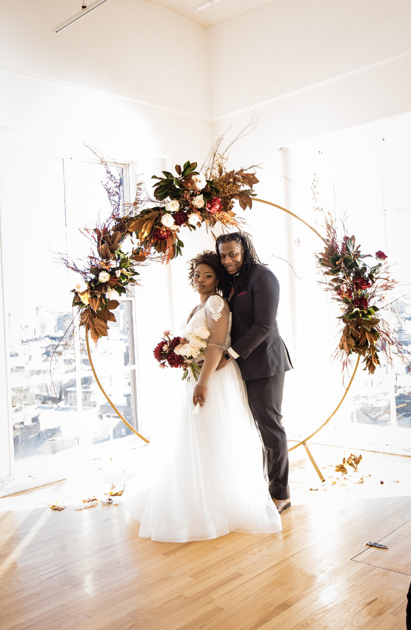 Beautiful light and airy photo of bride and groom next to an amazing floral arch