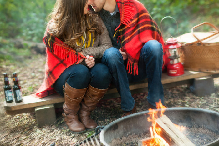 An engaged couple is sitting next to camp fire with a blanket draped around them.  About to kiss.