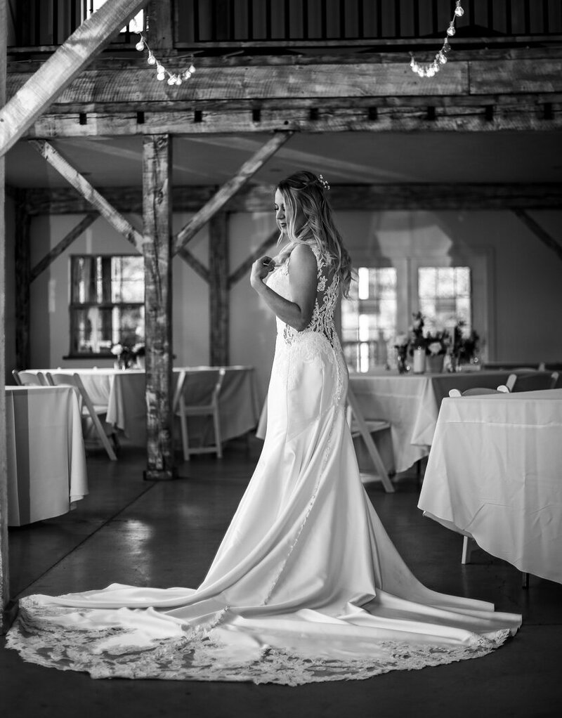 Solo portrait of bride standing in the barn set up for her Quincy Cellars wedding rception