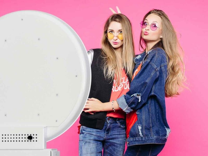 two girls posing front of a selfie stand