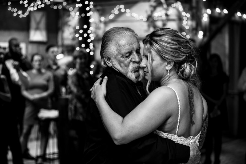 Father looks lovingly at bride during dance at Barn at Conneaut Creek