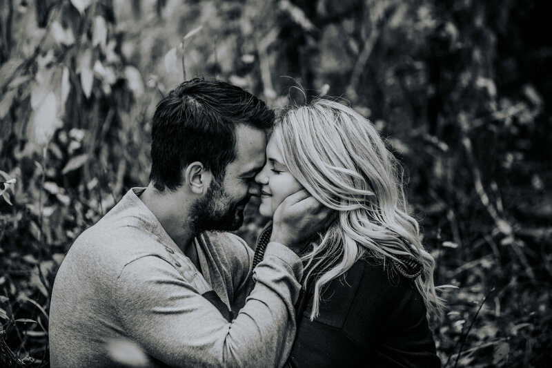 black and white  photo of couple  with man holding her face with eyes closed