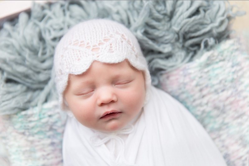 white wrapped newborn with white bonnet
