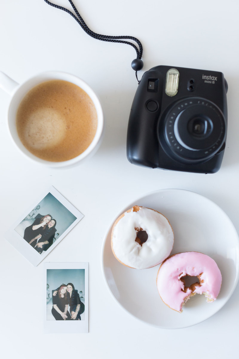 Coffee, donuts, and pictures of Britt and Kelsey of Launch Your Daydream on the desk in branding and website design studio for photographers