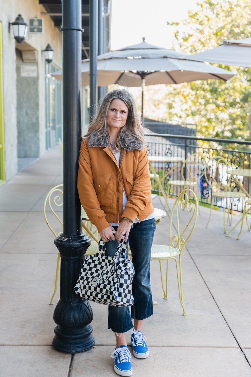 woman leaning against pole on cafe patio holding checkered bag