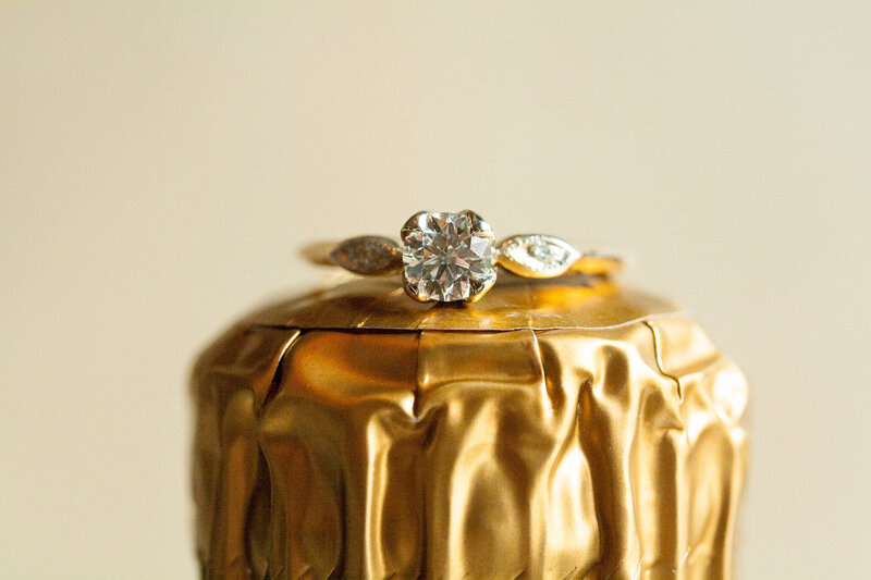 gold solitaire wedding ring on gold champagne bottle