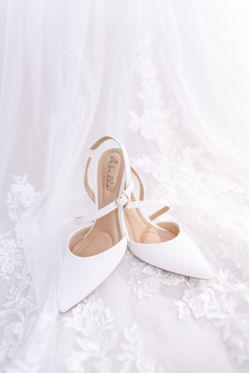 A pair of white bridal heels set atop a white, lace wedding dress.