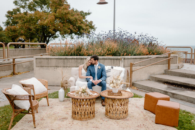 Bride & Groom sitting on a couch in a boho reception space set up outside
