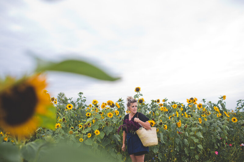 women holding a back while standing in a field of sunflowers