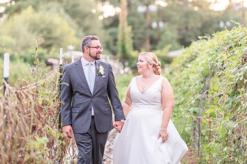 A light and airy photo of a couple walking through a garden after their wedding at the Chattahoochee Nature Center in Roswell Georgia.