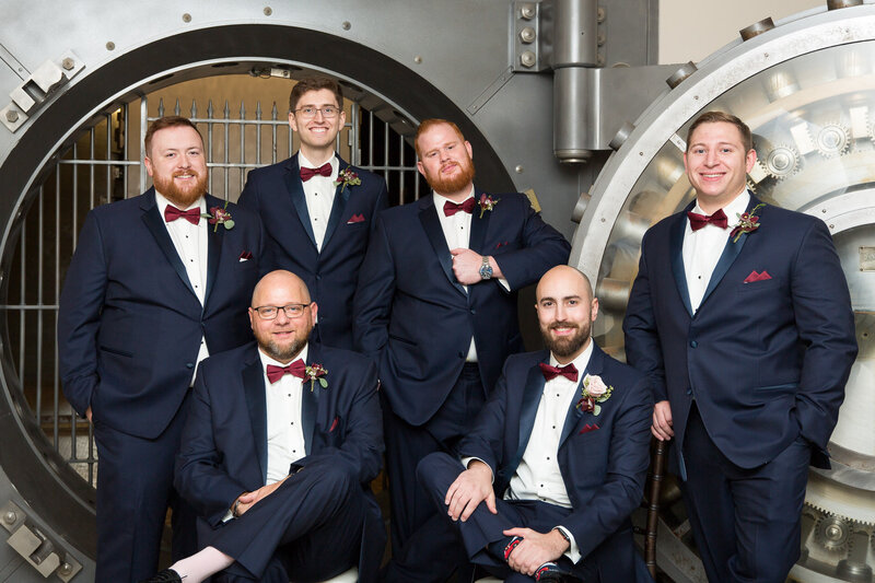 groomsmen in navy suits by bank safe at cityflats ballroom port huron