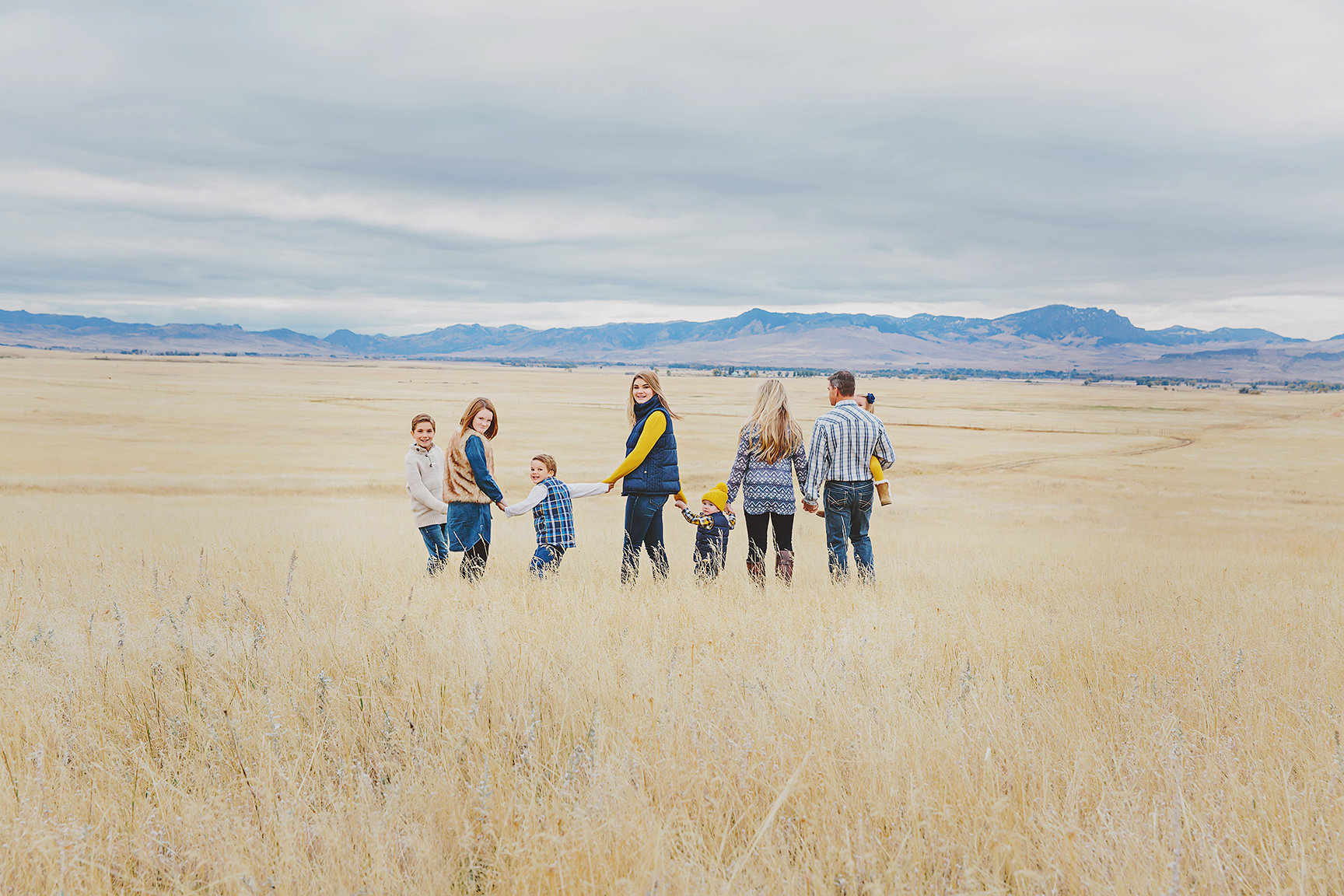 a family of 8 in a field showing fall colors, layers and testures