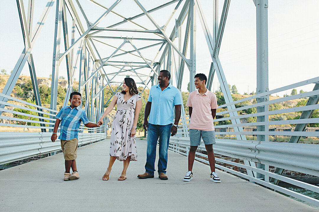 a family of 4 on a bridge wearing beautiful pastel colors
